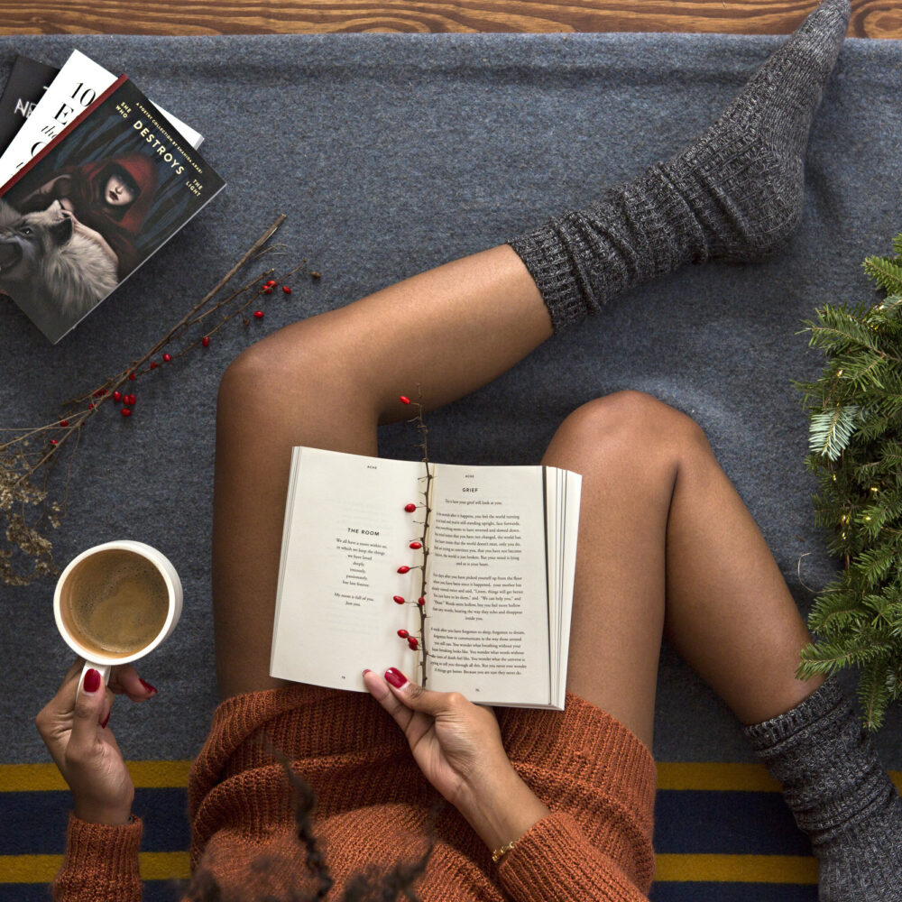holiday stress. Woman sitting on couch with to-do list and cup of coffee
