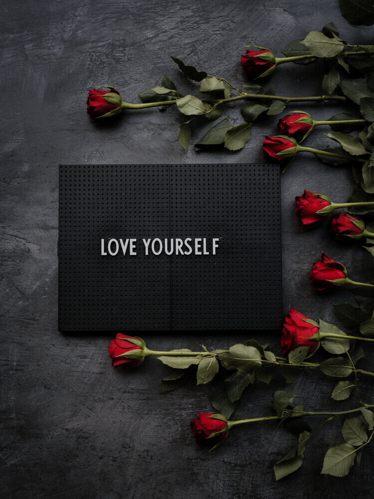 """self-care. Sign that reads """"Love Yourself"""" surrounded by red long-stem roses"""