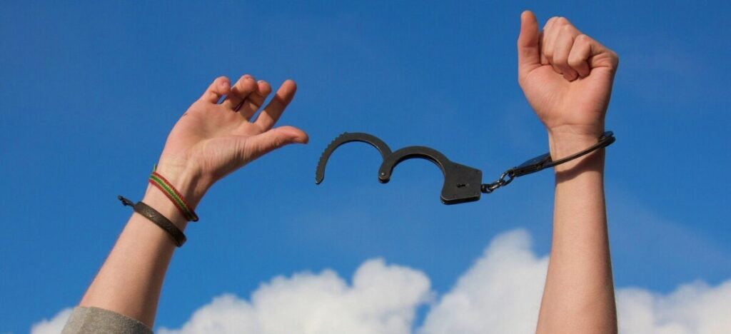 opioid use disorder. Hands breaking free of handcuffs